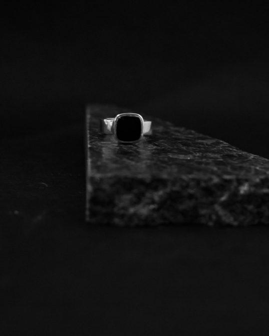 jaunā klasika ___izteikti vīrišķīgs zīmoggredzens ar sudrabā iesakutu kvadrāta formas oniksu.
